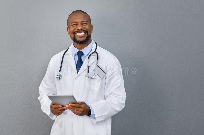Smiling doctor standing on grey wall royalty free stock photos