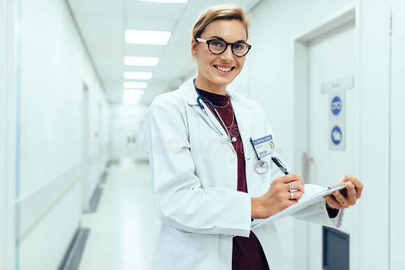 Smiling doctor standing in hospital corridor with clipboard stock photos