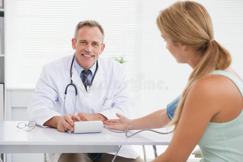 Smiling doctor taking patients blood pressure. In his office royalty free stock photo