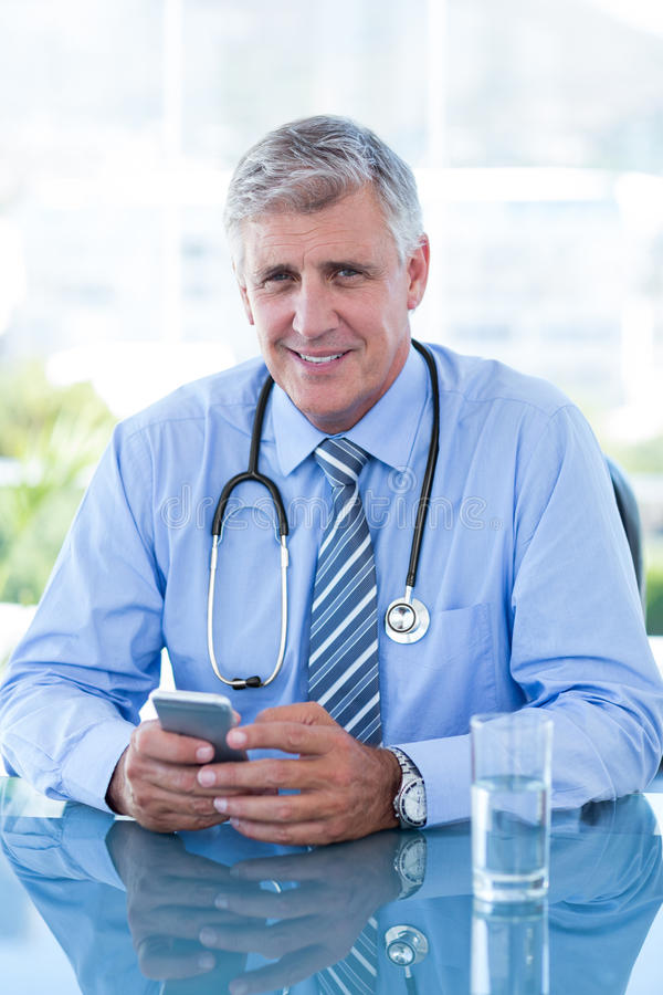 Smiling doctor texting with his mobile phone. In medical office royalty free stock image