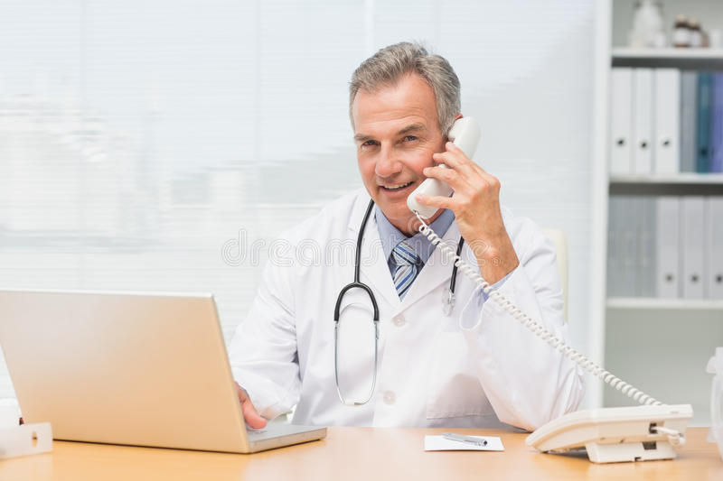 Smiling doctor using laptop and talking on phone at desk stock photo