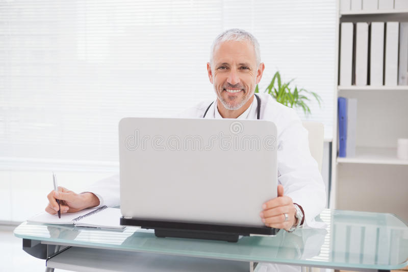 Smiling doctor using laptop and writing royalty free stock photography
