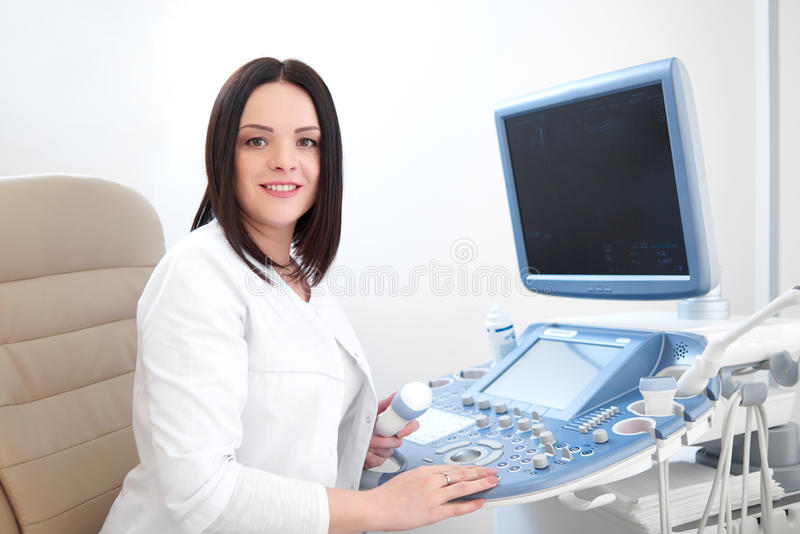 Smiling doctor using ultrasound equipment and computer. stock image