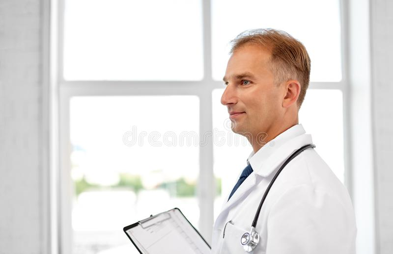 Smiling doctor in white coat at hospital royalty free stock images