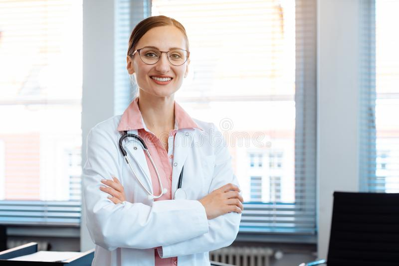 Smiling doctor woman in her office royalty free stock image