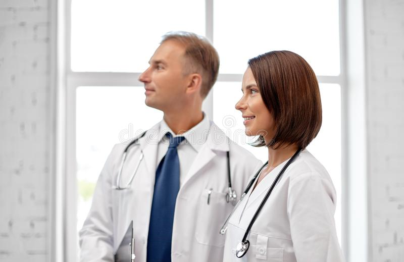 Smiling doctors in white coats at hospital stock photos