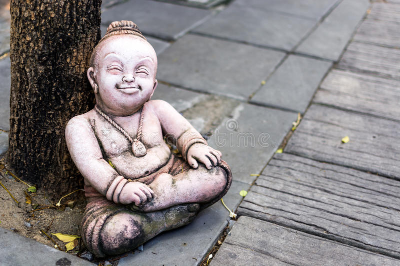 Smiling doll statue in the park. royalty free stock images