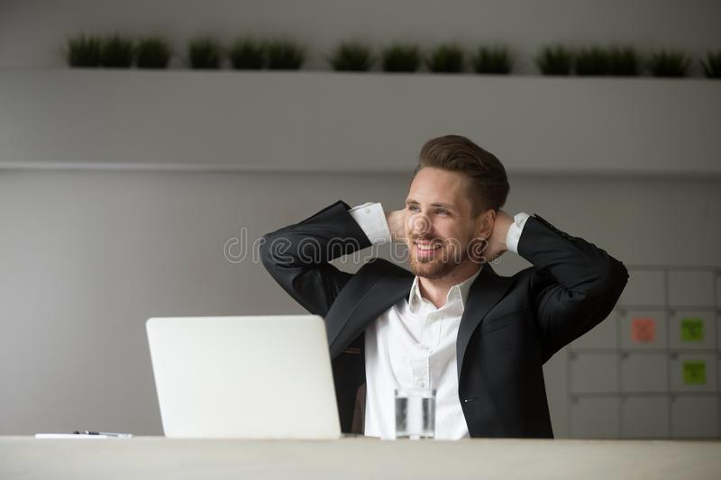 Smiling dreamy businessman resting hands behind his head. stock photos