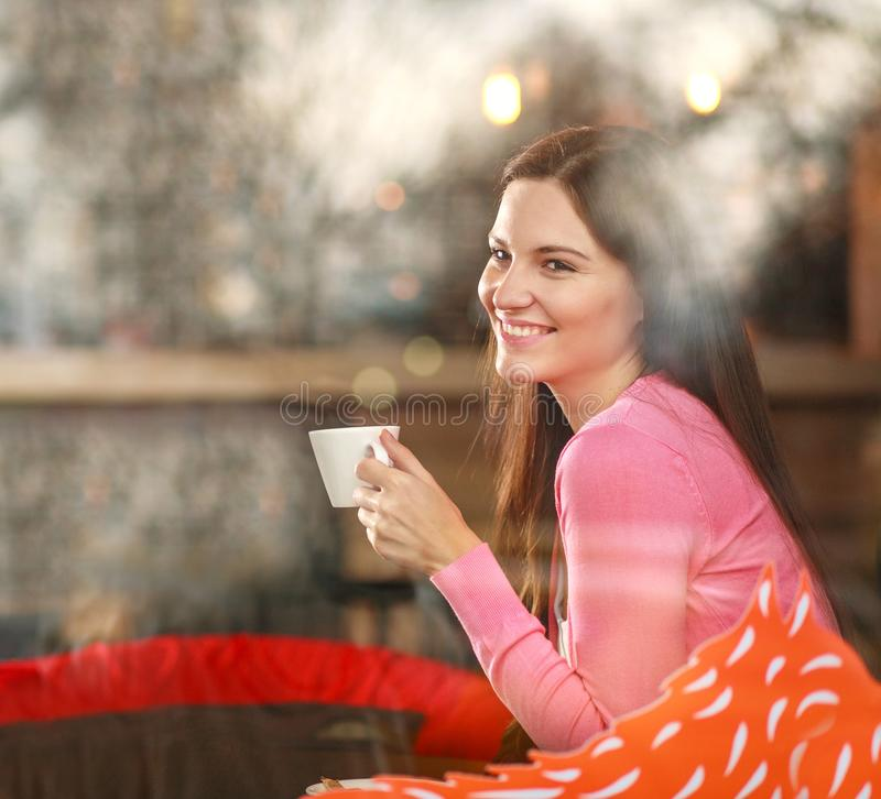 Smiling dreamy thoughtful woman in restaurant with cup of coffee, joyfully looking out, view through window with reflections royalty free stock photo