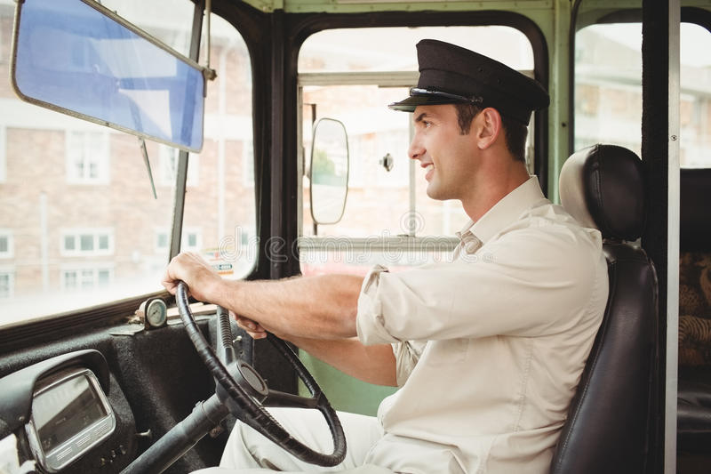 Smiling driver driving the school bus. Outside the elementary school stock photography