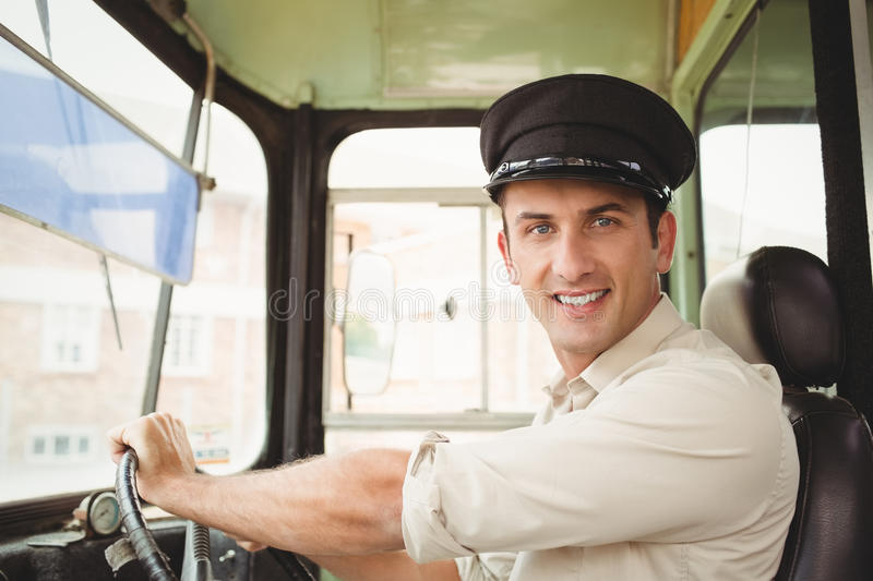 Smiling driver driving the school bus. Outside the elementary school stock photo