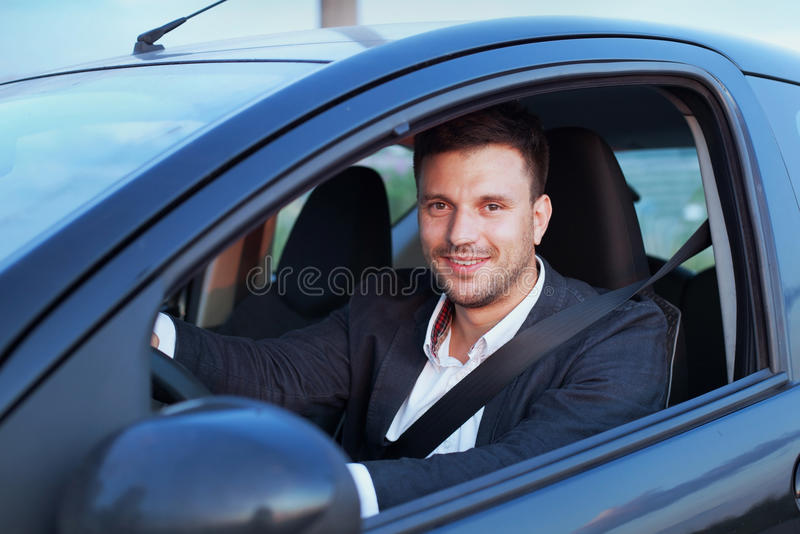 Smiling driver. Happy smiling driver in the car, portrait of young successful business man stock images