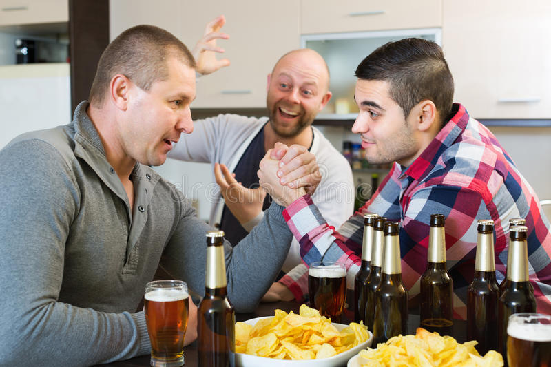 Smiling and drunk men armwrestling. Smiling and drunk adult men armwrestling, their friend supporting stock image