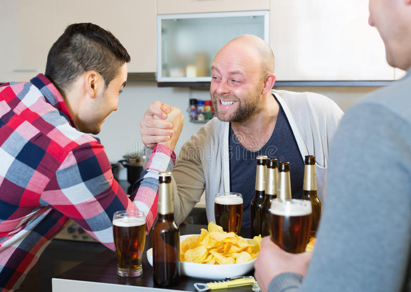 Smiling and drunk men armwrestling. Their friend supporting stock photography
