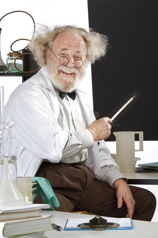 Smiling eccentric scientist points to blackboard royalty free stock image