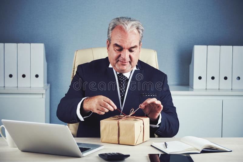 Smiling elderly businessman opening present. Smiling excited happy mature male in dark elegant suit sitting at office workplace and unpacking gift in box wrapped stock photography