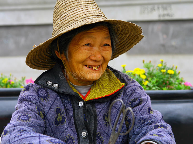 Smiling elderly chinese woman in a straw hat. WUDANSHAN, CHINA - OCT 31, 2007: Smiling elderly chinese woman in a straw hat. In recent years, the average life stock image