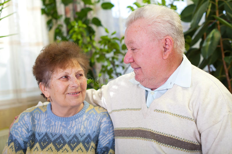 Smiling elderly couple at home. Picture of a smiling elderly couple at home stock photos