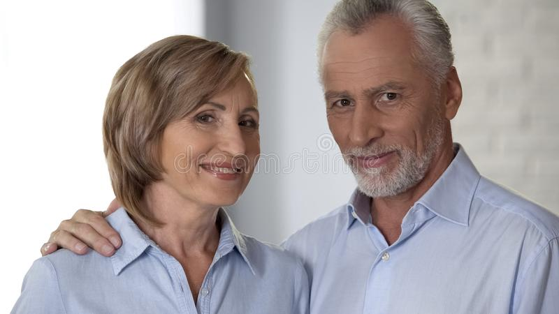Smiling elderly couple looking at camera, man hugging lady, harmony in relations royalty free stock photo