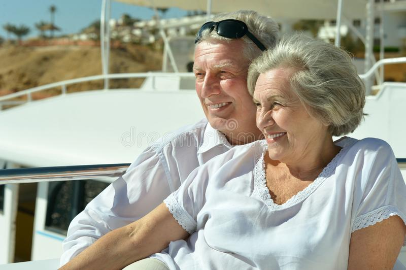 Elderly couple resting on yacht. Smiling elderly couple resting on yacht in sea royalty free stock photo
