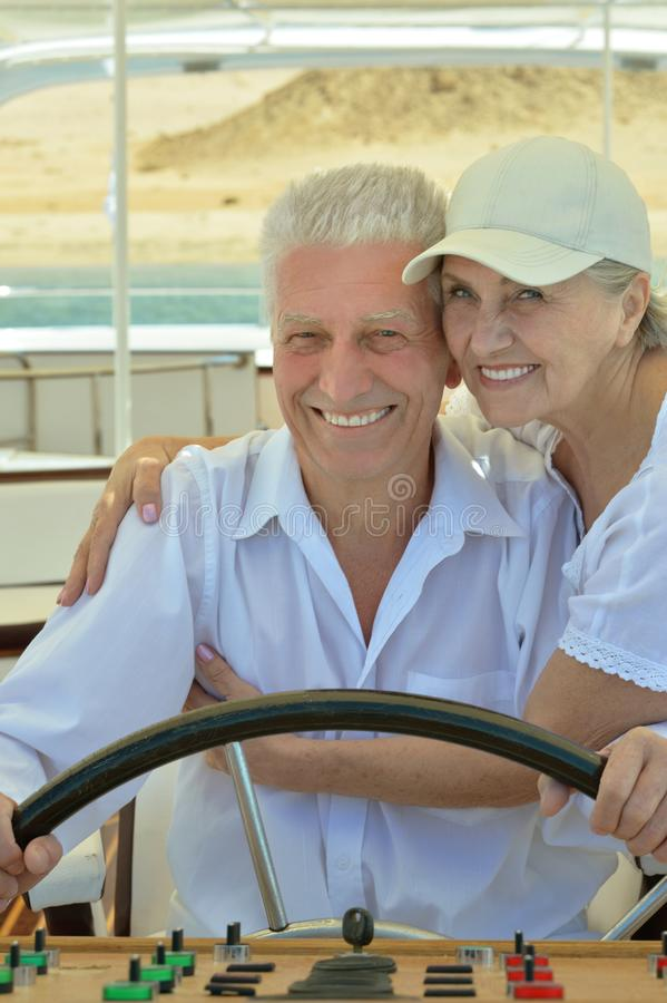 Smiling elderly couple resting on yacht royalty free stock photos