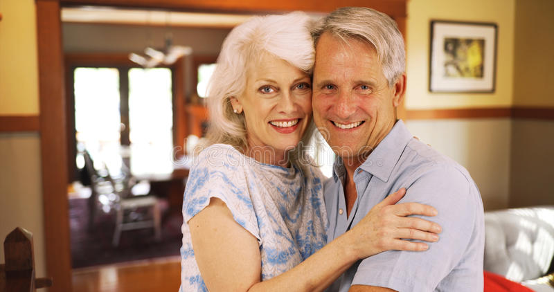 Smiling elderly couple sitting at home looking at camera royalty free stock photo