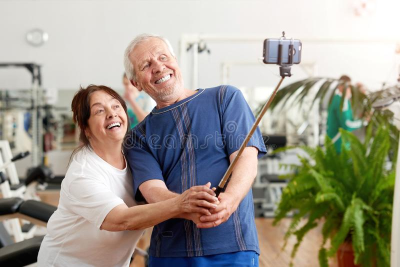 Smiling elderly couple taking selfie at gym. royalty free stock images