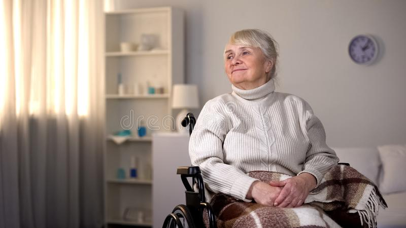 Smiling elderly female sitting wheelchair covered blanket, happy clinic patient stock image