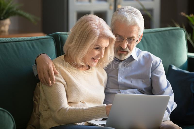 Smiling aged spouse spending free time on sofa with computer. stock photography