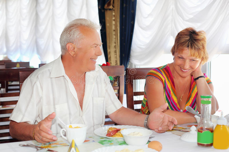Smiling elderly having breakfast at restaurant. Smiling elderly married couple having breakfast at restaurant near window,Talk with each other stock photos