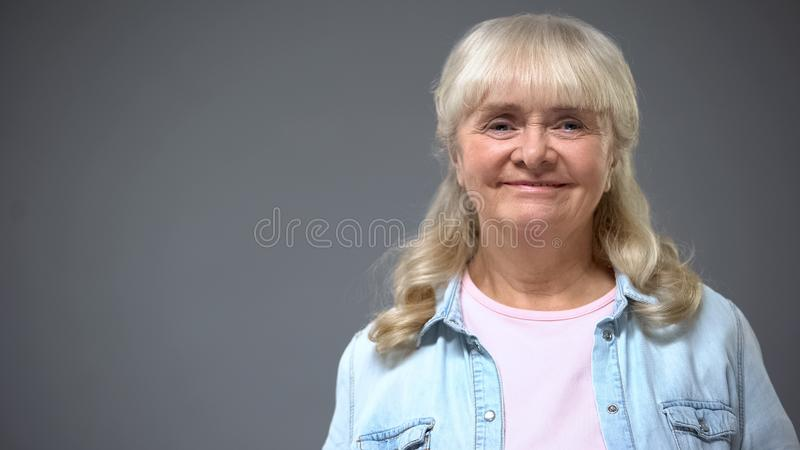 Smiling elderly lady in casual clothes isolated on gray, happy secure old age royalty free stock photo