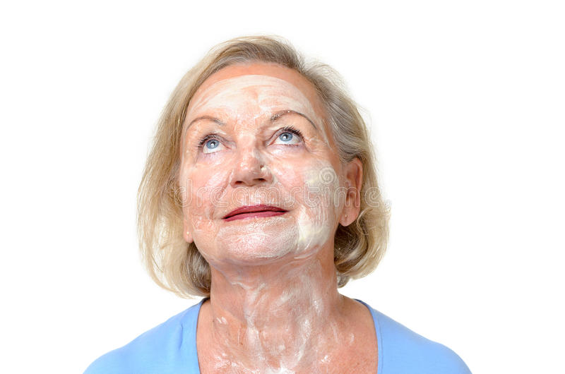 Smiling elderly lady with face cream on her skin stock photo