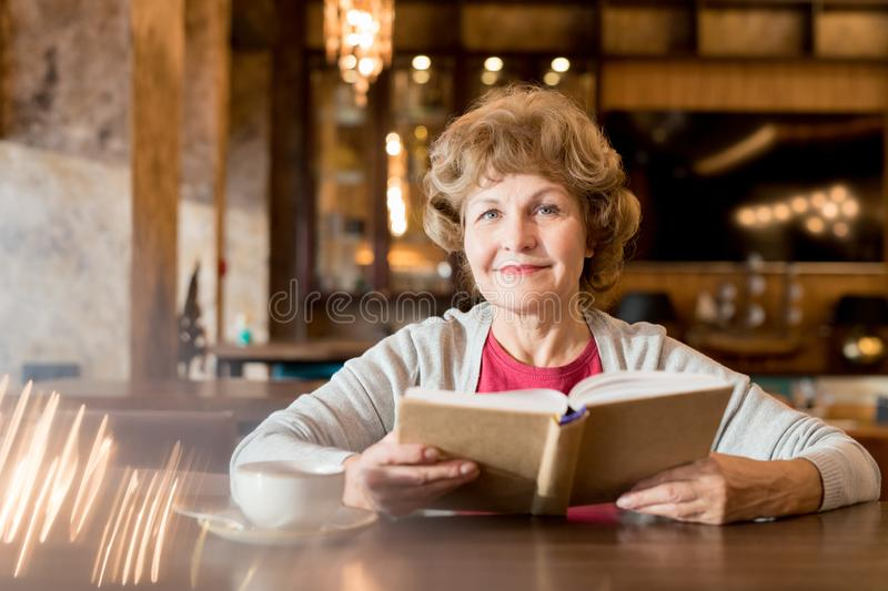 Smiling elderly lady reading favorite book in cafe stock photo