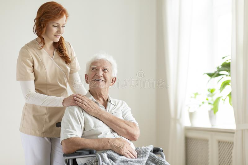 Smiling elderly man in a wheelchair and friendly caregiver in a. Smiling elderly men in a wheelchair and friendly caregiver in a nursing house stock photo