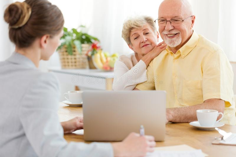 Smiling elderly man and woman purchasing a trip at the travel ag stock image