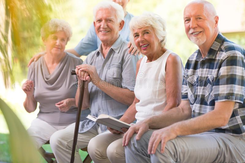 Smiling elderly people at patio. Smiling elderly people spending time together at the patio of nursing house royalty free stock photo