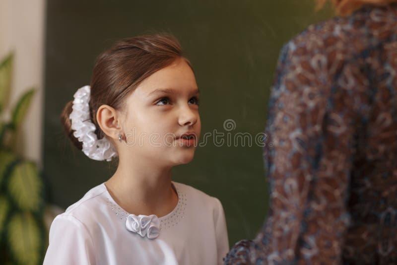 Smiling elderly teacher near the chalkboard asking student at the math lesson stock image