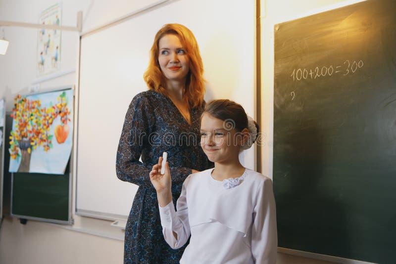 Smiling elderly teacher near the chalkboard asking student stock photo