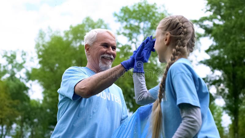 Smiling elderly volunteer with granddaughter collecting garbage giving high five. Stock photo royalty free stock photo