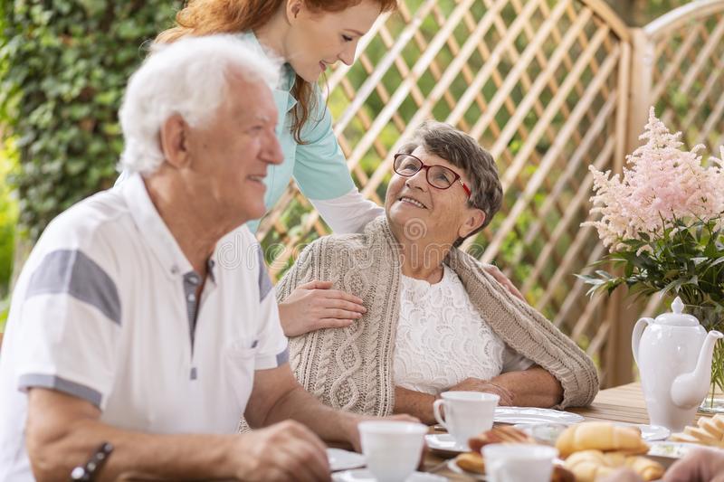 Smiling elderly woman and caregiver during meeting for lunch on. Smiling elderly women and caregiver during meeting for lunch on the terrace royalty free stock image