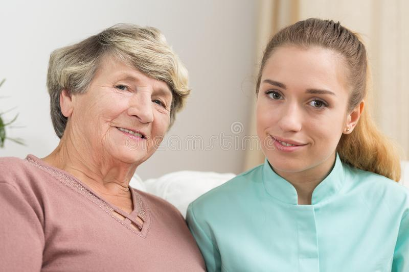Smiling elderly woman and caregiver. Portrait of smiling elderly women and helpful caregiver royalty free stock images