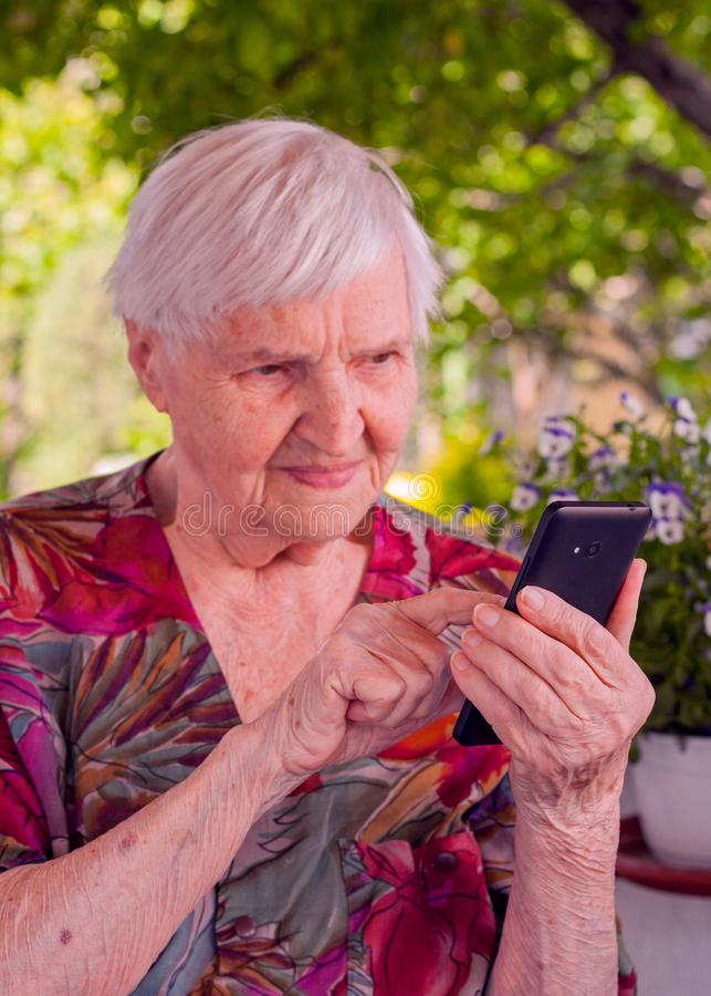 Smiling elderly woman dialing phone number royalty free stock photo