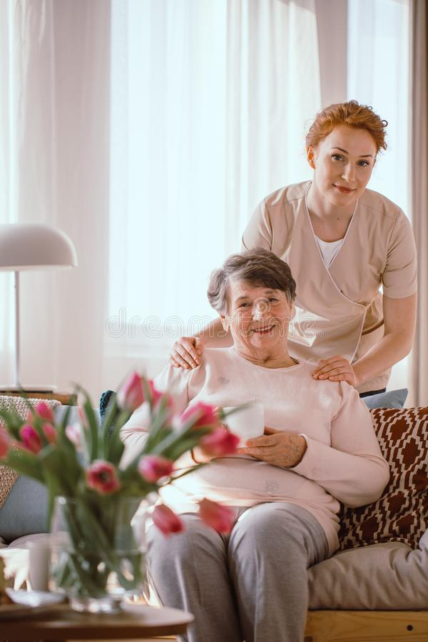 Smiling elderly woman drinking tea with her caregiver in the retirement home royalty free stock images
