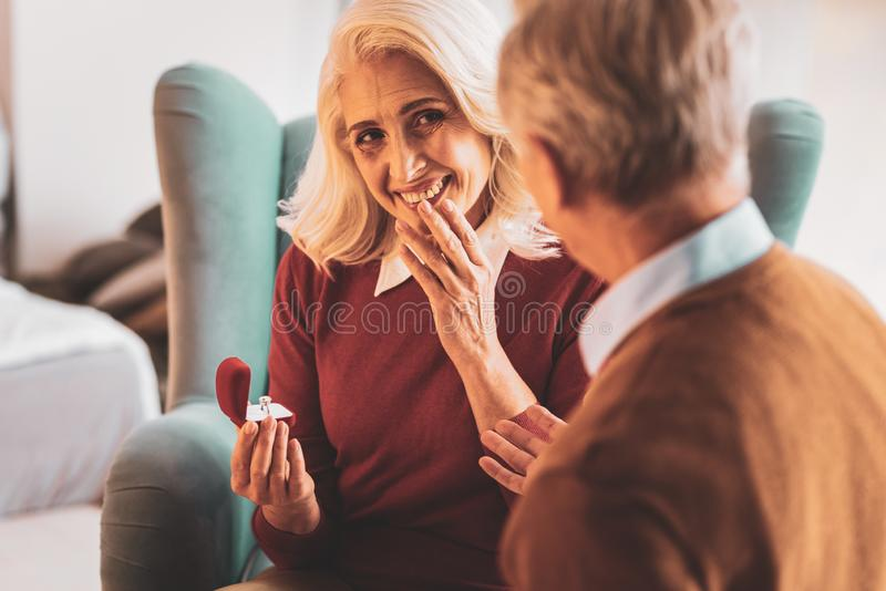 Smiling elderly woman feeling excited receiving ring royalty free stock images