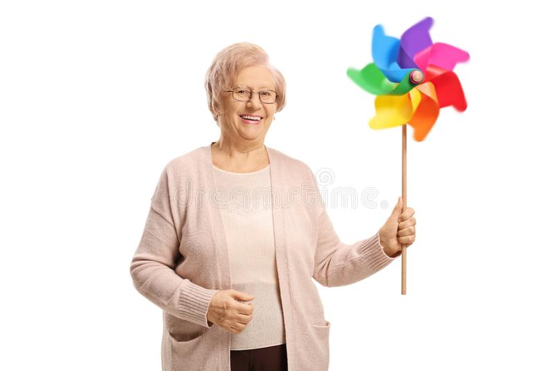 Smiling elderly woman holding a spinning pinwheel royalty free stock images
