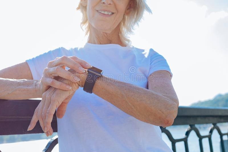 Smiling elderly woman looking at her smart watch royalty free stock photography