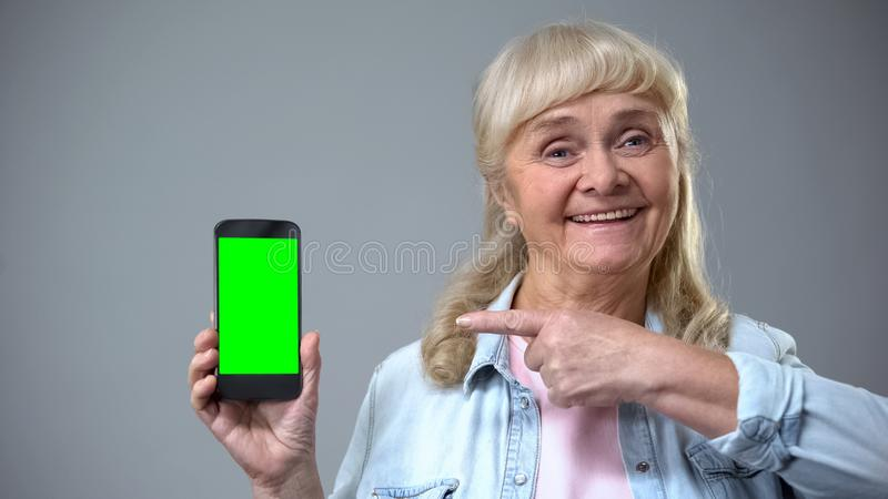 Smiling elderly woman showing smartphone with green screen, advertisement stock photos