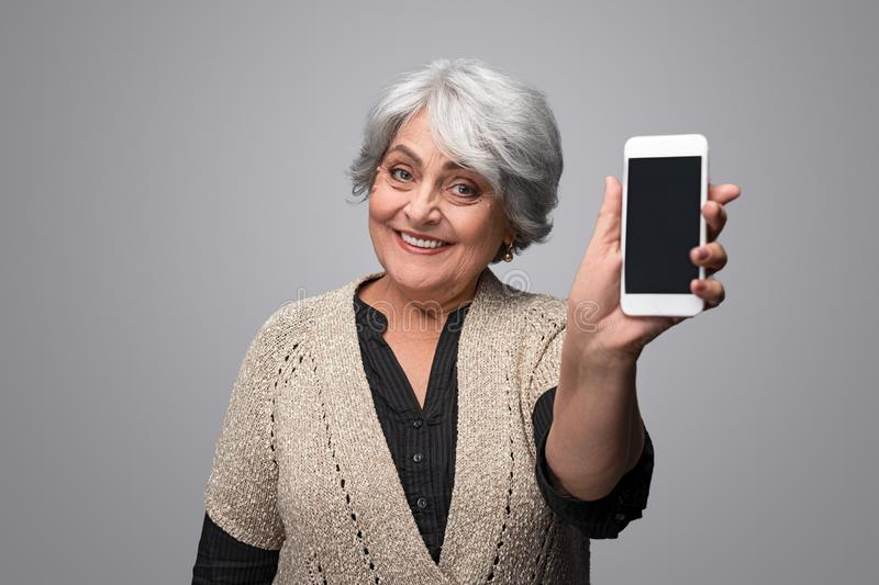 Smiling elderly woman showing smartphone stock photo