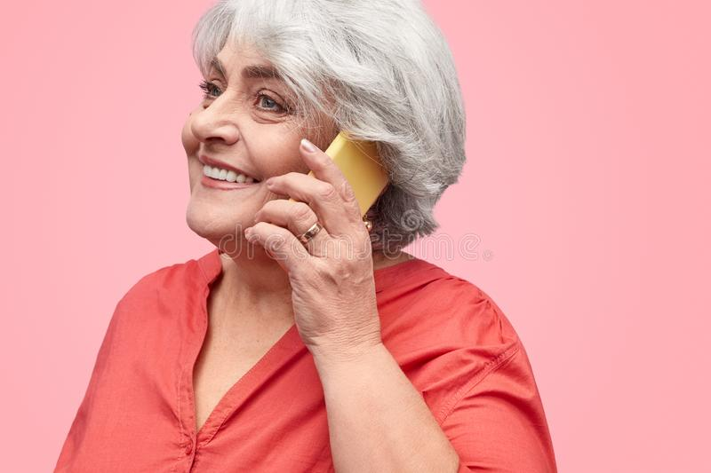 Smiling elderly woman talking on phone royalty free stock photography