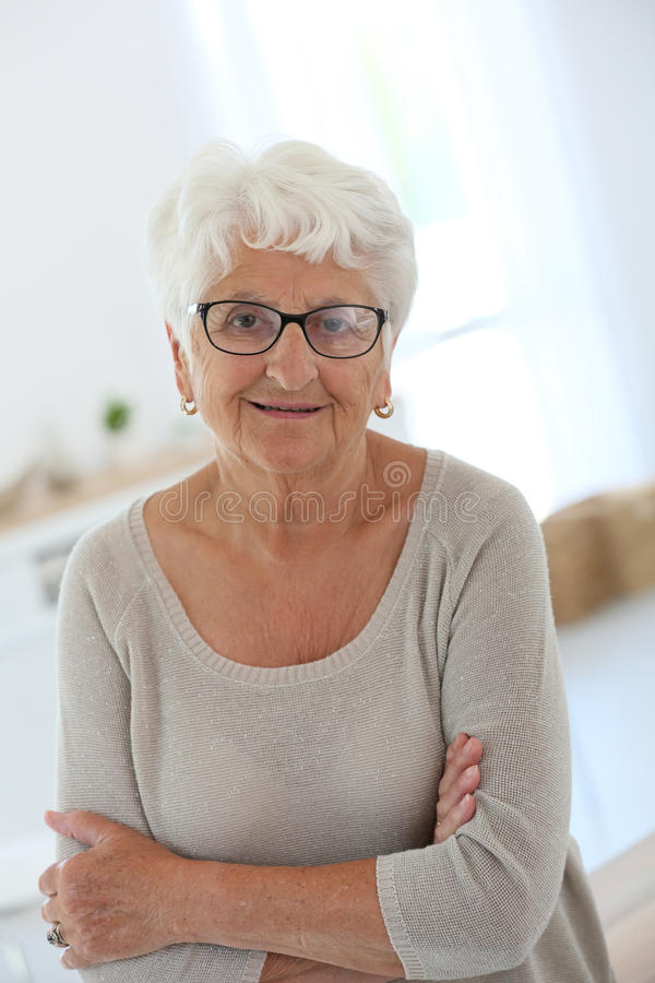 Smiling elderly woman with trendy eyeglasses royalty free stock photography